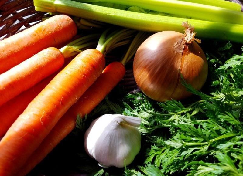 ingredients in basket - carrots, celery, onion, garlic