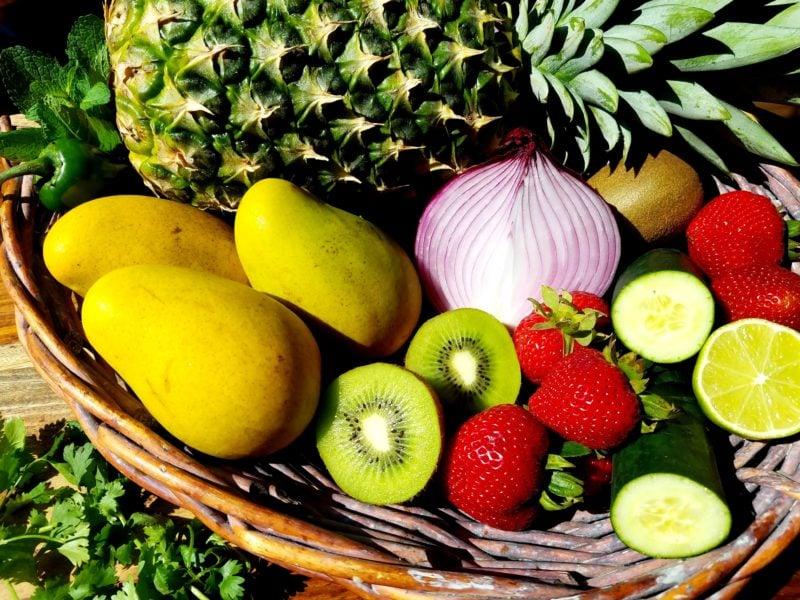 Whole pineapple, mango, kiwi, strawberries, cucumber, jalapeno, lime, cilantro and mint in wicker basket.