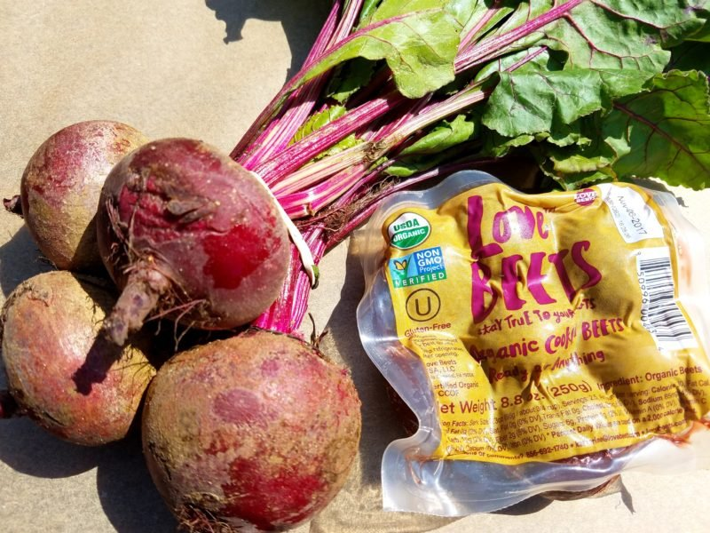 Fresh beets and packaged beets on table.