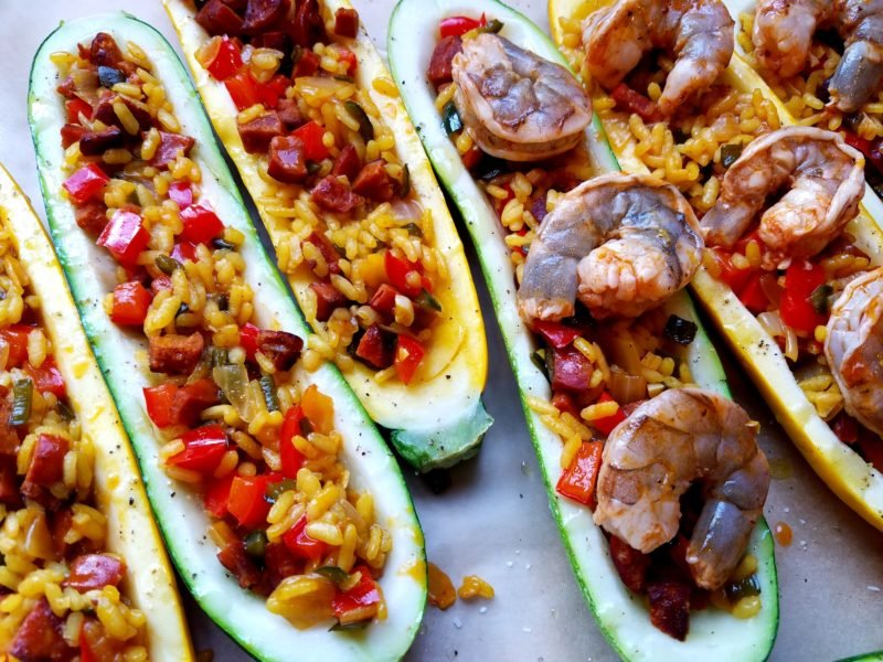 Zucchini boats filled with paella and shrimp ready to go in the oven.
