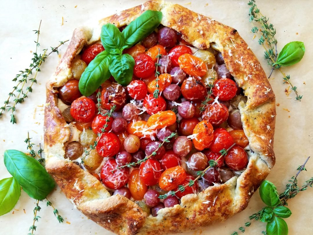 Blistered Cherry Tomato & Grape Galette | giveitsomethyme.com – a delicious tomato and grape galette recipe with whipped ricotta and goat cheese all swaddled in a savory herb crust! #tomatogalette #cherrytomatogalette #tomatogaletterecipe #tomatogalettegoatcheese #grapegalette #giveitsomethyme