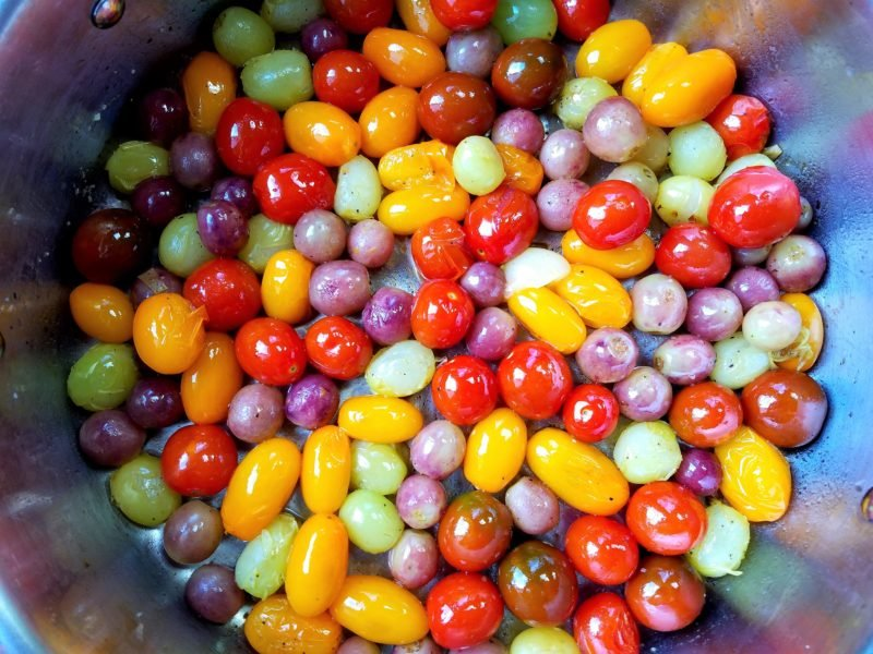 tomatoes and grapes beginning to blister in skillet