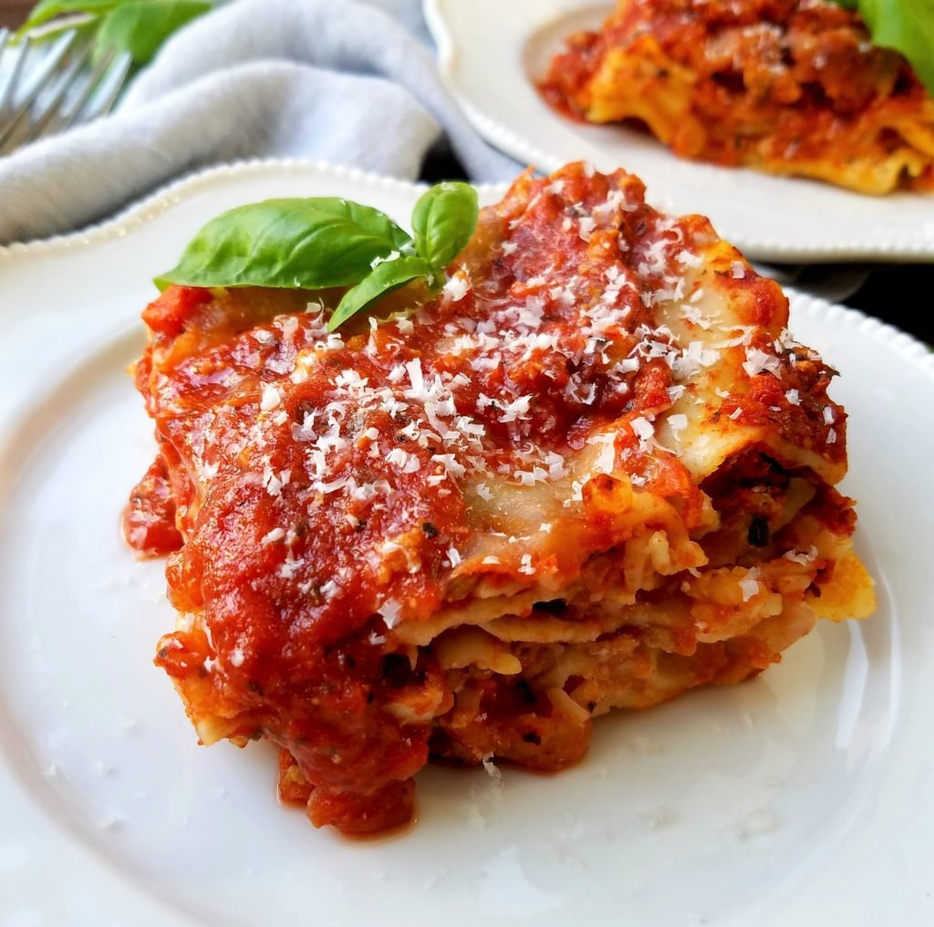 Lasagna Served - Give it Some Thyme - a delicious make-ahead, crowd-pleasing recipe that combines all the great flavors of a traditional bolognese with a tad less guilt using ground turkey and turkey sausage. #lasagna #lasagnarecipe #homemadelasagna #turkeylasagna #pastadinner #pastadinnerrecipes #pastadinnerideas #pastadinnerparties #falldinnerideas #falldinnerrecipes #giveitsomethyme