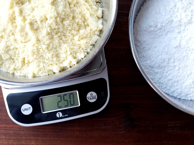 Almond flour and powdered sugar measured on a kitchen scale.