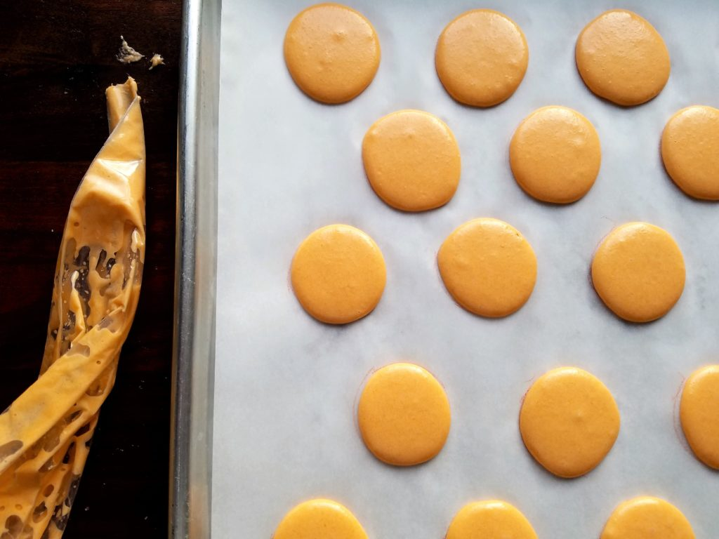 Macarons Piped onto Prepared Parchment Lined Baking Sheet