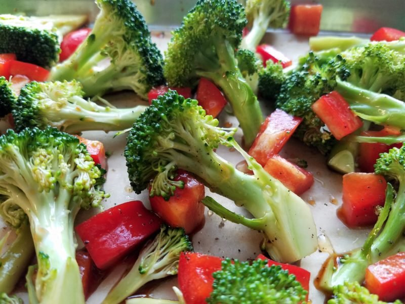 Broccoli florets and red bell pepper on ready to roast.