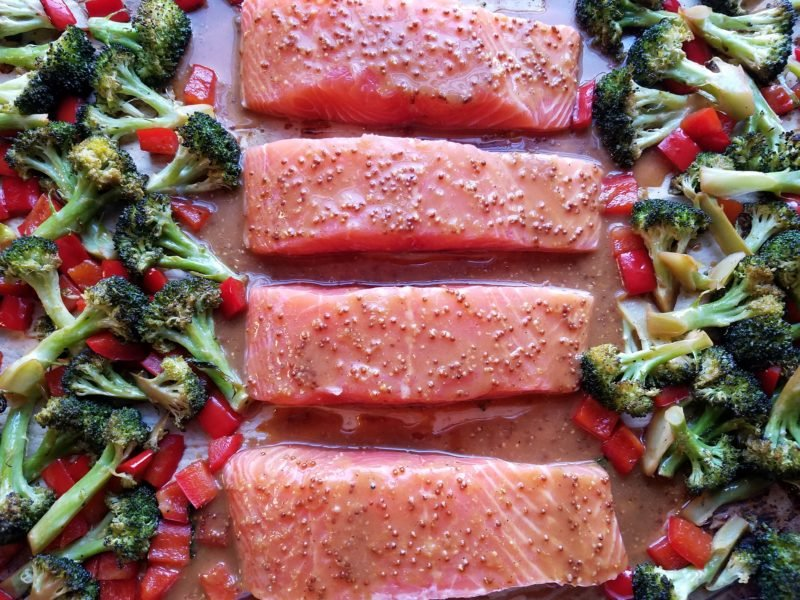 Glazed salmon fillets on sheet pan with vegetables ready for the oven.