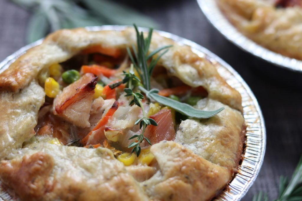 Individual Chicken Pot Pie | Give it Some Thyme - a simple, flaky herb crust swaddles chunks of tender rotisserie chicken and vegetables bathing in a smooth gravy flavored with sage, rosemary and thyme. #chickenpotpie #chickenpotpieeasy #homemadechickenpotpie #homemadechickenpotpierecipe #comfortfooddinners #comfortfoodrecipes #giveitsomethyme