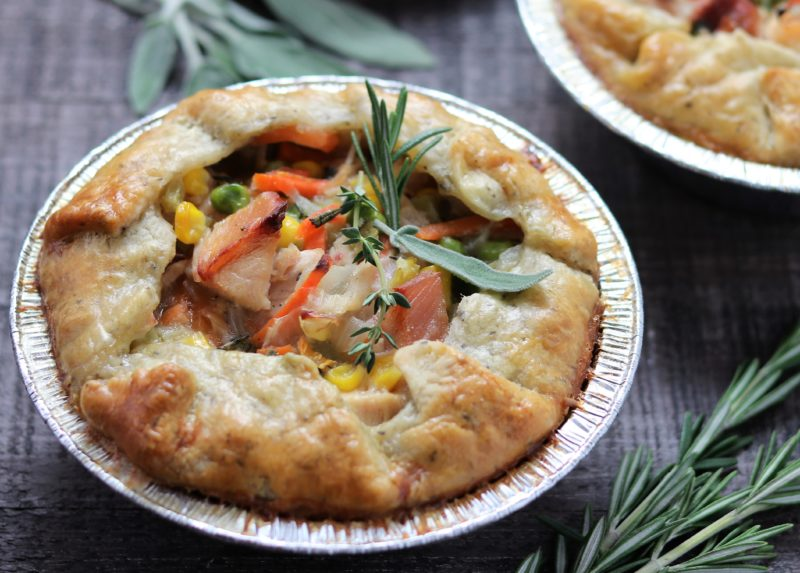 Individual Chicken Pot Pies | giveitsomethyme.com - a simple, flaky herb crust swaddles chunks of tender rotisserie chicken and vegetables bathing in a smooth gravy flavored with sage, rosemary and thyme. #chickenpotpie #chickenpotpieeasy #homemadechickenpotpie #homemadechickenpotpierecipe #comfortfooddinners #comfortfoodrecipes #giveitsomethyme