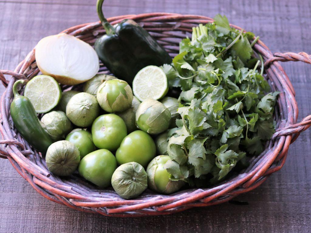 Salsa Verde Ingredients shown in Basket - tomatillos, poblano, jalapeño , lime, onion and cilantro