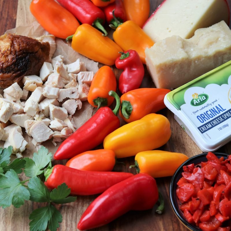 ingredients spread out on wooden cutting board - mini peppers, chopped chicken, cheeses and roasted peppers