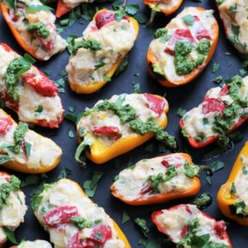 Creamy Chicken Stuffed Mini Peppers with Spinach Walnut Pesto | Give it Some Thyme - sweet little bells loaded with bubbling cheese, tender chicken, roasted peppers, and shallots then drizzled with a tasty spinach pesto! #stuffedpeppers #chickenstuffedpeppers #ministuffedpeppers #ministuffedpeppersappetizers #spinachpesto #appetizers #fingerfood #superbowlfood #gamedayfood #partyfood #glutenfree #ketofriendly #giveitsomethyme