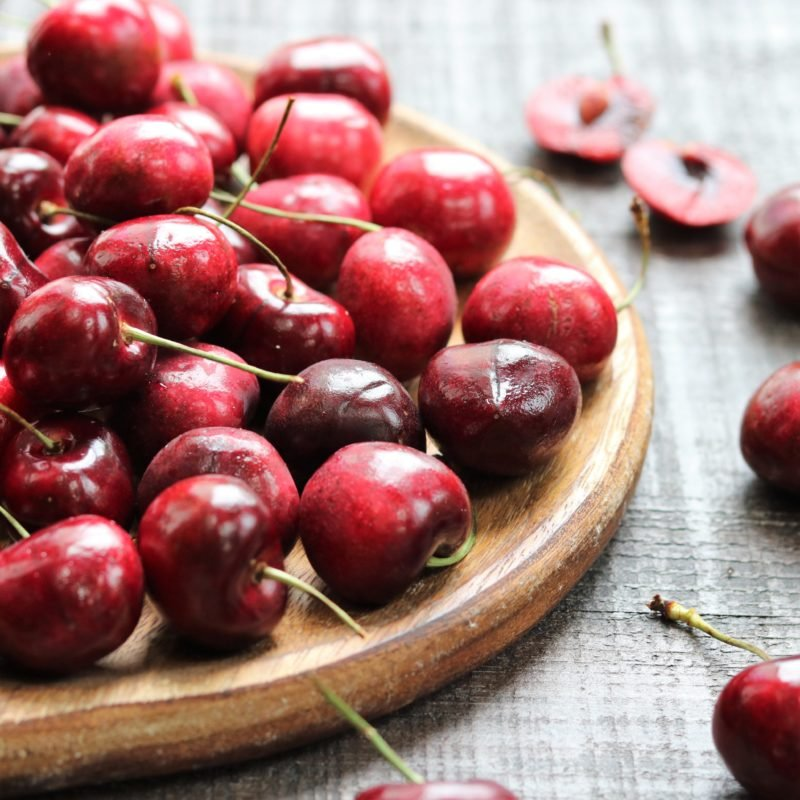 Fresh cherries on wooden charger.