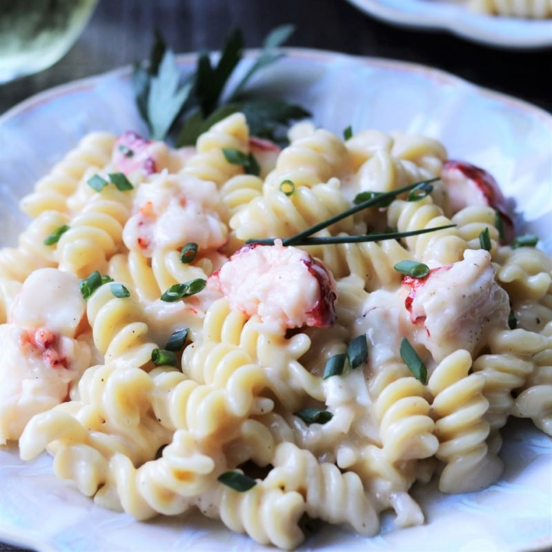 Lobster and Shrimp Mac and Cheese garnished with chopped chives and served on scalloped off-white plate.