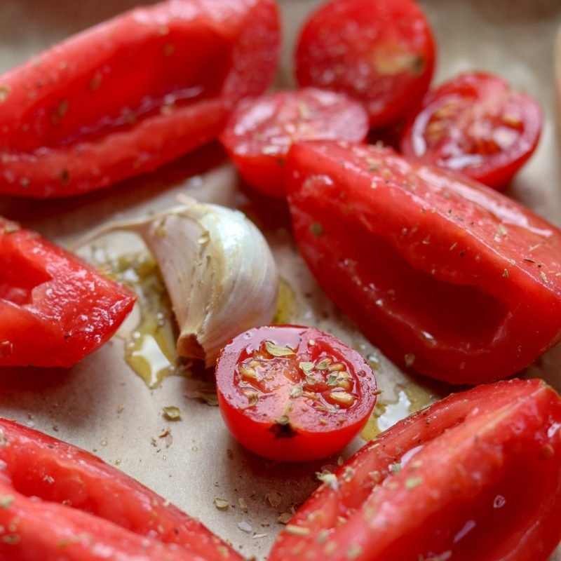 Tomatoes and garlic drizzled with olive oil ready to roast.