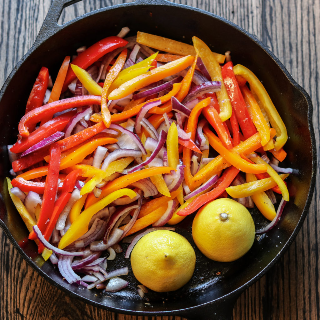 Bell Peppers, Onion and Lemon Halves in Skillet