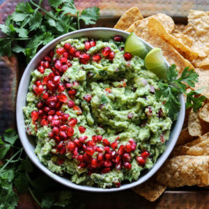 Festive Holiday Pomegranate Guacamole - Give it Some Thyme – ripe avocados, pomegranate arils, queso fresco, lime juice, and fresh herbs come together deliciously in this twist of the classic Mexican dip! #guacamole #guacamoleeasy #guacamolerecipe #guacamolediprecipes #pomegranateguacamole #pomegranateguacamolerecipe #pomegranate #giveitsomethyme
