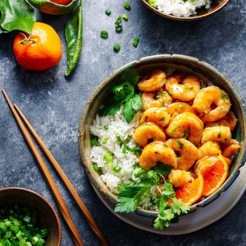 Orange & Honey Glazed Shrimp served in a rustic bowl over rice.