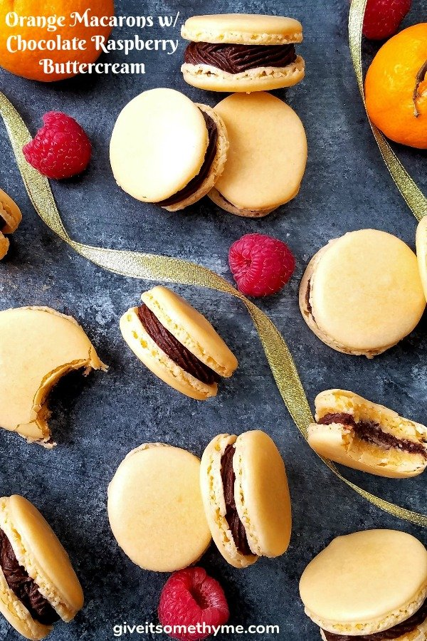 Orange Macarons w/ Chocolate Raspberry Buttercream | Give it Some Thyme - tender, chewy little sandwiches laced with orange extract and filled with a smooth, luscious chocolate raspberry buttercream! #macarons #macaronsrecipe #macaronshowtomake #christmasmacarons #frenchmacarons #frenchmacaronsrecipe #orangemacarons #christmascookies #christmascookierecipe #giveitsomethyme