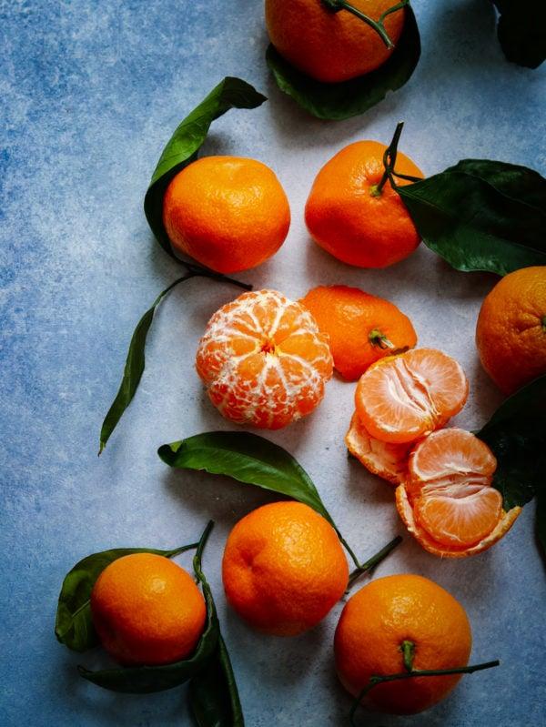 Satsuma oranges on blue surface.