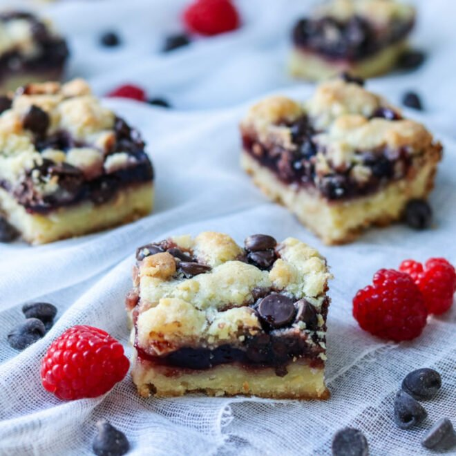 Bars are cut and displayed on cheesecloth with fresh raspberries and chocolate chips.