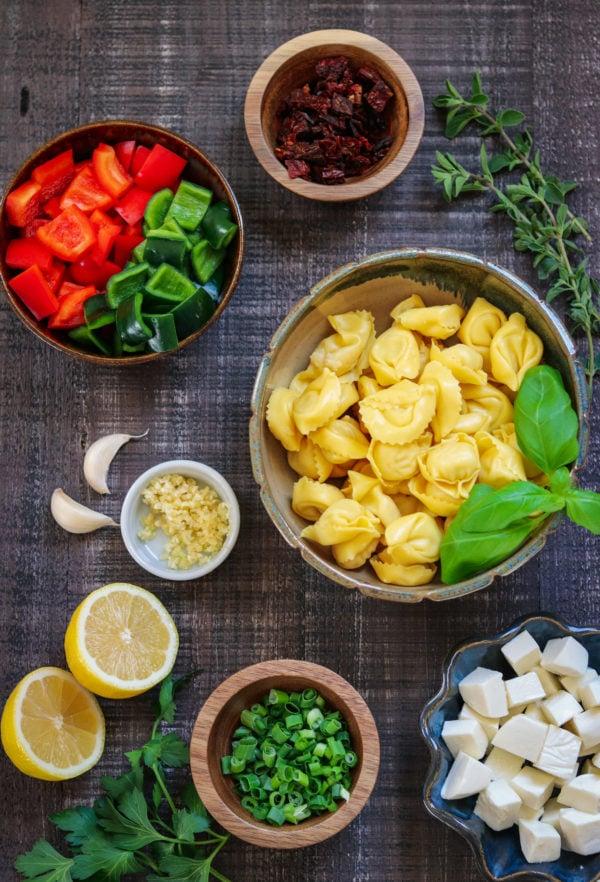 Tortellini Skewers Ingredients in bowls on wooden surface.