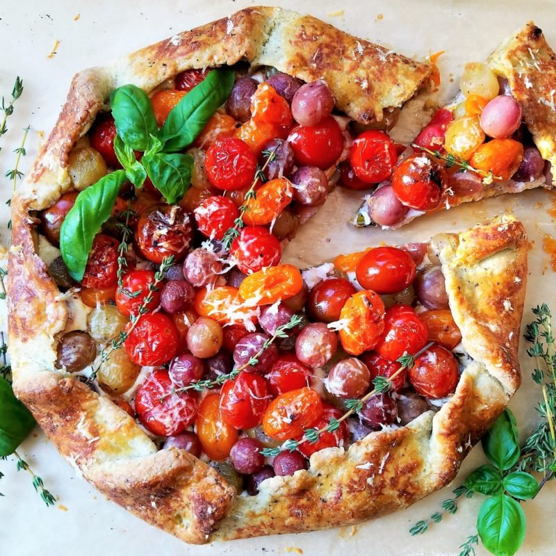 Blistered Cherry Tomato + Grape Galette | Give it Some Thyme – a delicious tomato and grape galette recipe with whipped ricotta and goat cheese all swaddled in a savory herb crust! #tomatogalette #cherrytomatogalette #tomatogaletterecipe #tomatogalettegoatcheese #grapegalette #galette #galetterecipe #galetterecipesavory #galetterecipeeasy #giveitsomethyme
