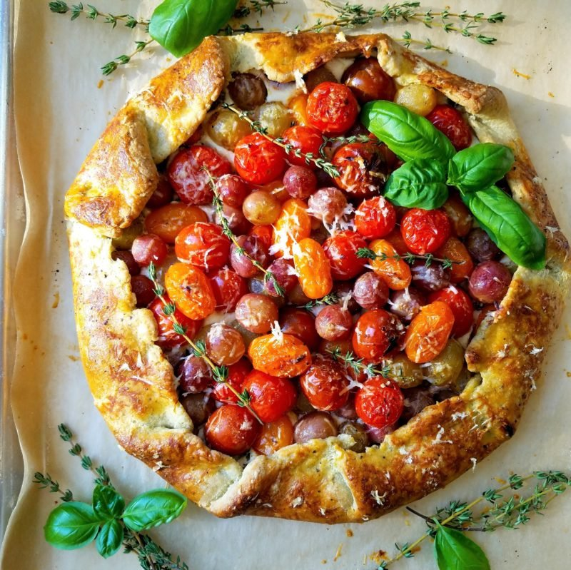 Blistered Cherry Tomato and Grape Galette | Give it Some Thyme – a delicious tomato and grape galette recipe with whipped ricotta and goat cheese all swaddled in a savory herb crust! #tomatogalette #cherrytomatogalette #tomatogaletterecipe #tomatogalettegoatcheese #grapegalette #galette #galetterecipe #galetterecipesavory #galetterecipeeasy #giveitsomethyme