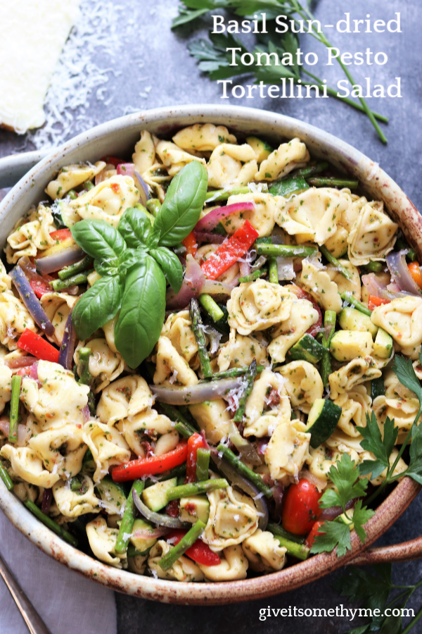 Basil Sun-dried Tomato Pesto Tortellini Salad | Give it Some Thyme – an easy and delicious side dish recipe loaded with fresh roasted vegetables and coated in a deliciously intense pesto. A crowd-pleaser for year round entertaining you can make ahead! #tortellinisalad #tortellinisaladrecipes #tortellinisaladpesto #pastasalad #pastasaladrecipes #pastasaladforacrowd #pesto #basilpesto #sundriedtomatopesto #sundriedtomatorecipes #giveitsomethyme