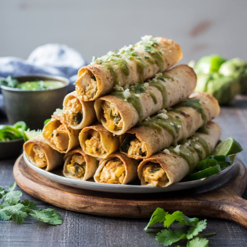 Roasted Chicken Verde Taquitos | giveitsomethyme.com – Full of tender rotisserie chicken, bubbling mexican cheese, salsa verde, veggies and spices! Perfect for game days! #taquitos #chickentaquitos #chickentaquitosbaked #easytaquitoschicken #bakedtaquitos #mexicantaquitos #mexicanfood #superbowlfood #gamedaysnacks #gamedayappetizers #roastedtaquitos #salsaverde #giveitsomethyme