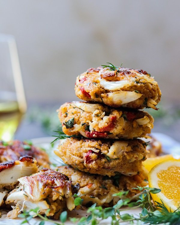 Jumbo Lump Crab Cakes Stacked – succulent high lump crab-to-breading ratio cakes served with a silky, luscious citrusy sauce. #appetizers #springrecipe #summerrecipe #lightdinners #lightdinnersforsummer #crabcakes #crabcakesrecipe #meyerlemon #chardonnaysauce #winesauce #giveitsomethyme | giveitsomethyme.com