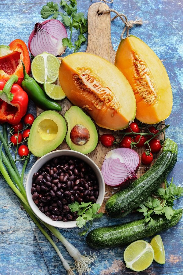 Ingredients displayed - black beans, cantaloupe, zucchini, red bell pepper, red onion, cherry tomatoes, green onions, lime, avocado and cilantro