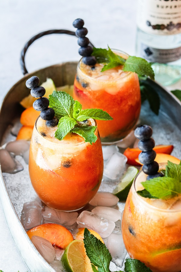 4th of July Party Menu Ideas - Gingered Peach & Blueberry Mojitos - beat the heat with a refreshingly flavorful twist to the classic cocktail! #mojitos #cocktails #cocktailrecipes #mocktails #peachrecipes #blueberries #summerrecipes #giveitsomethyme | giveitsomethyme.com