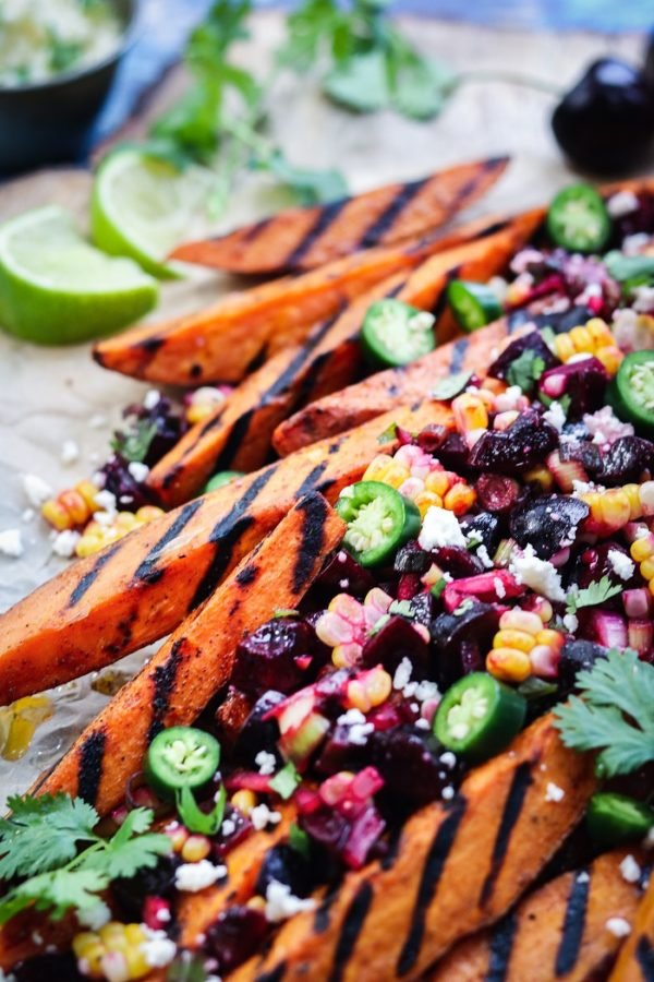 Close up of sweet potato fries topped with cherry salsa.
