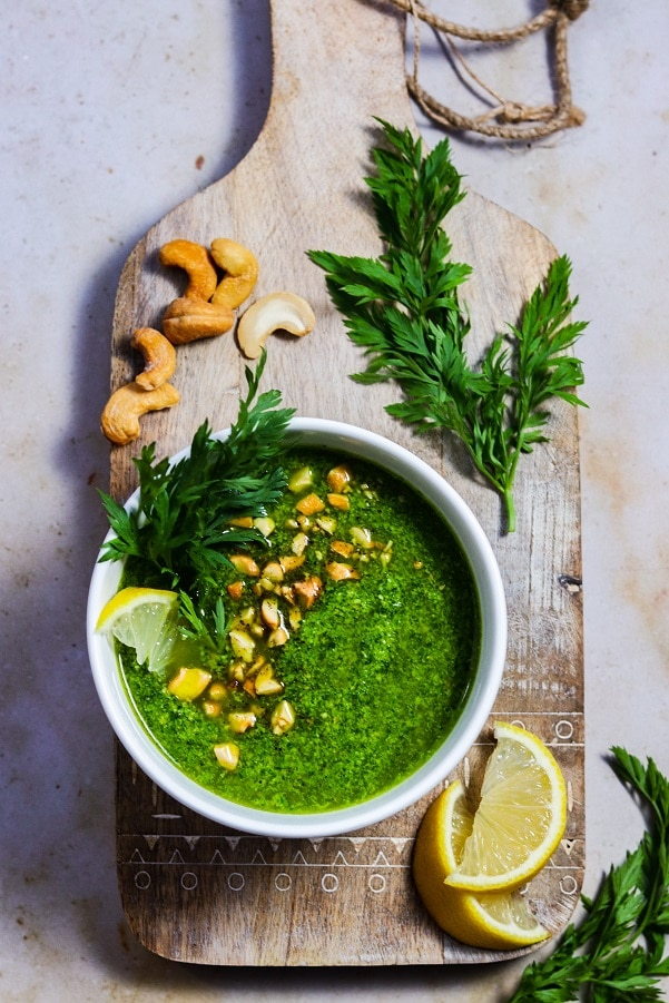 Pesto served in white bowl on wooden board garnished with cashews, carrot tops and lemon wedges.
