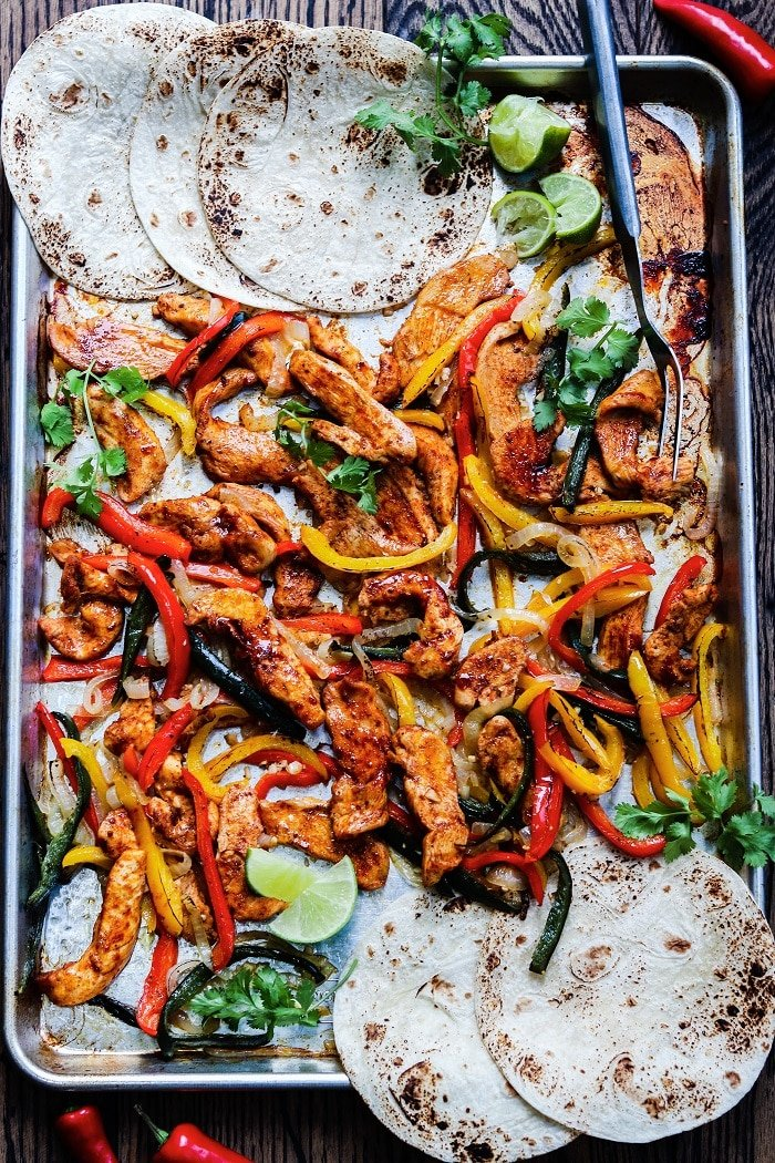 Fajitas served on sheet pan with charred tortillas, lime wedges and cilantro.