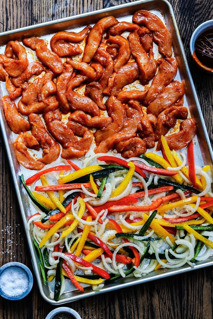Chicken, peppers and onion on sheet pan ready to bake.
