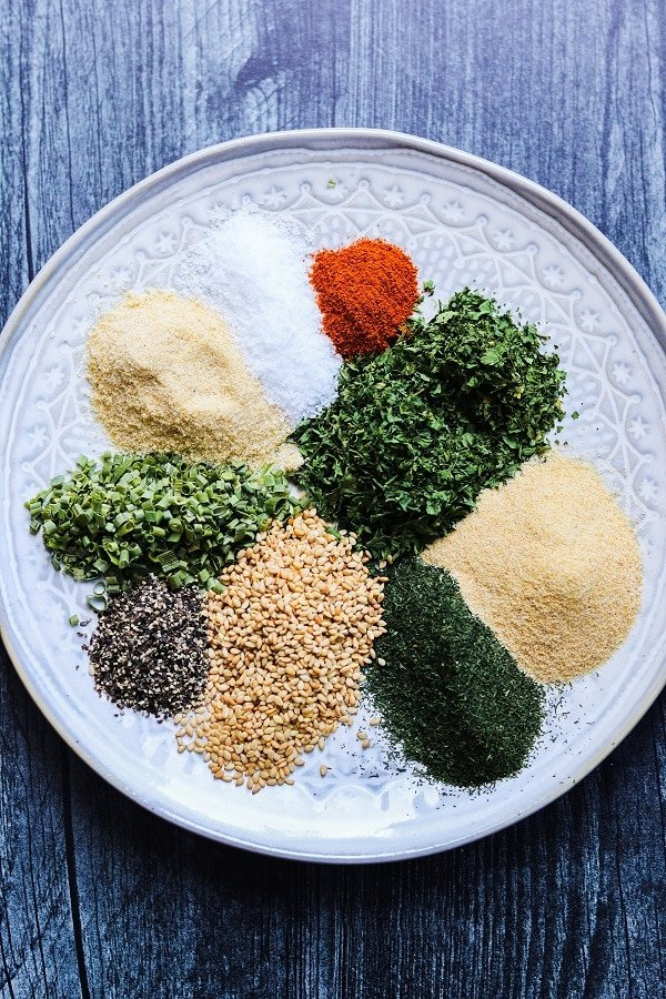 dried spices on plate - parsley, dill, chives, garlic powder, onion powder, salt, black and cayenne pepper and sesame seeds