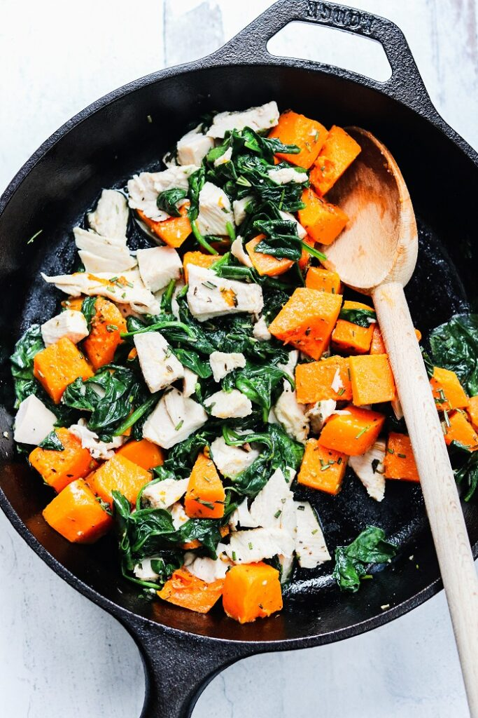 turkey, butternut squash and spinach cooking in skillet