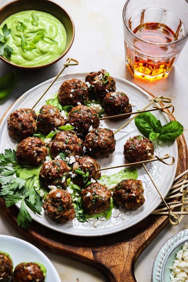 Greek Lamb Meatballs with Creamy Green Herb Sauce served on white plate with wooden charger underneath and plenty of toothpicks.