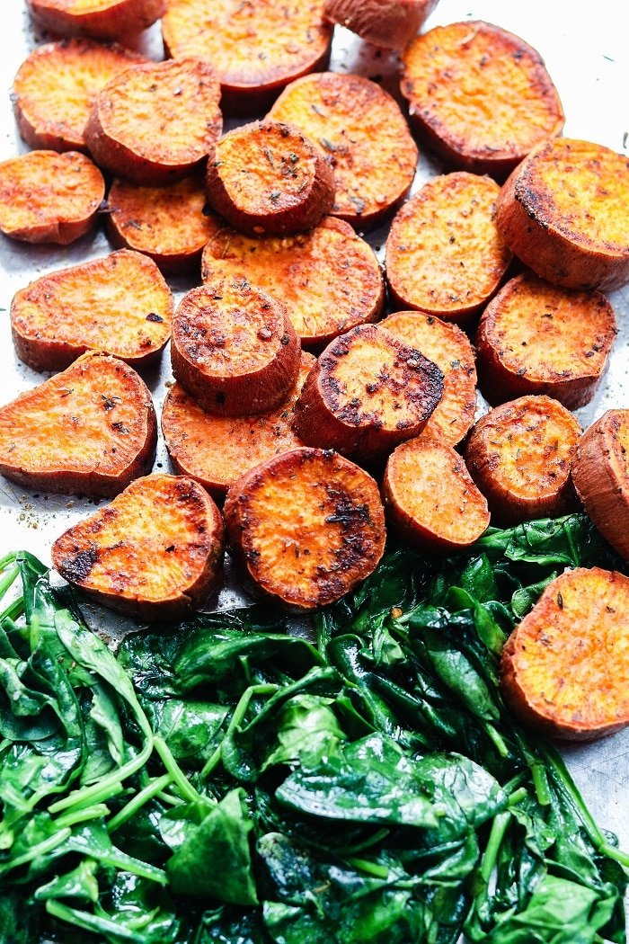 jerk-spiced sweet potatoes and spinach cooked on sheet pan