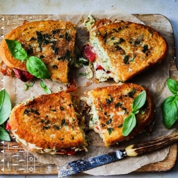 Italian Grilled Cheese w/ Pesto Whipped Ricotta & Herb Butter | giveitsomethyme.com – Layers of flavor abound in this four-cheese grilled cheese taking one of our favorite guilty pleasures to a whole new level.