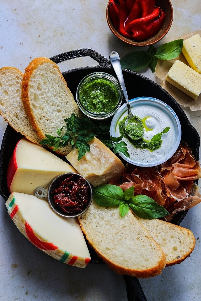 ingredients arranged in skillet: four cheeses, bread, herbs, prosciutto, roasted peppers, pesto and butter