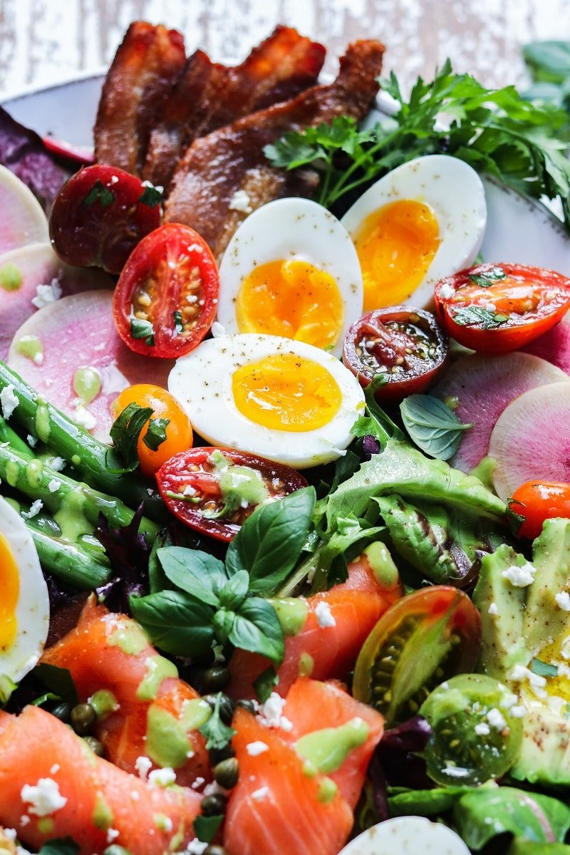 Close up of soft boiled eggs, cherry tomatoes and herbs