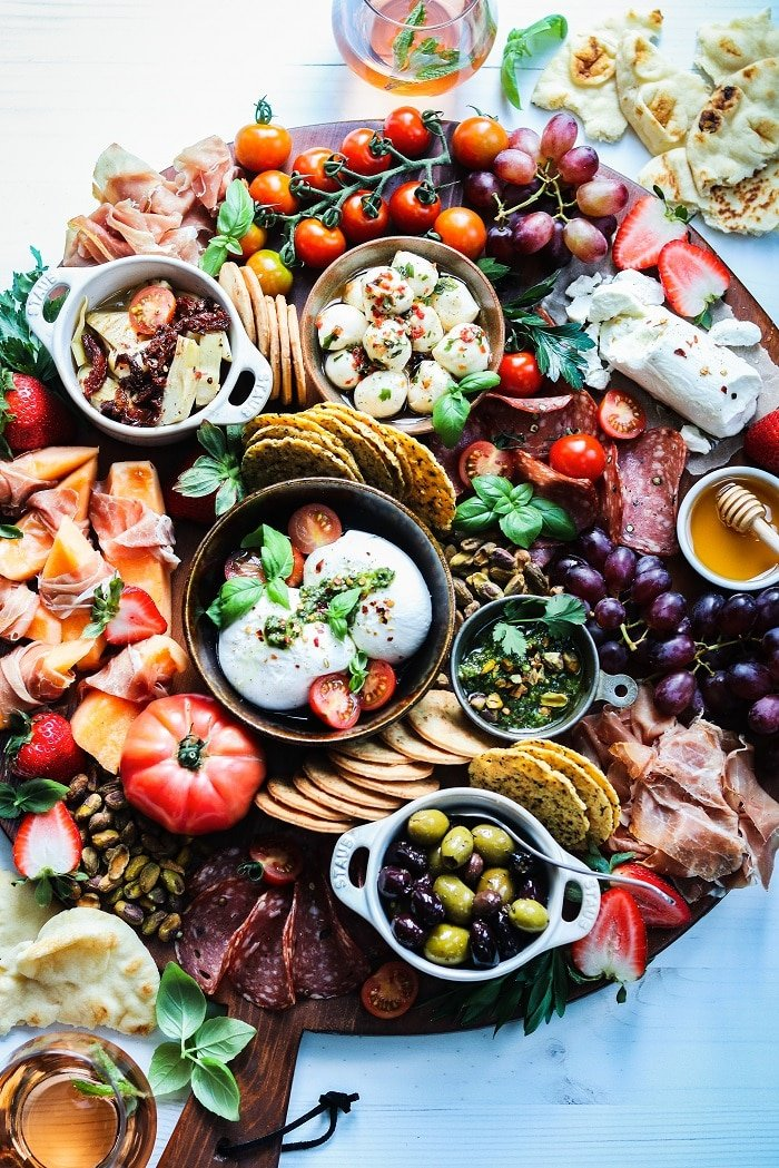 Weekend Snacking Cheese & Charcuterie Board | giveitsomethyme.com – Relax and enjoy this seasonal snack board loaded with cheeses, Italian meats, fruits, veggies and fresh pesto. Check out the tips for pulling your own board together in minutes! #charcuterie #charcuterieboard #cheeseboard #charcuterieboardideas #snackboard #snacking #fingerfoods #appetizers #giveitsomethyme