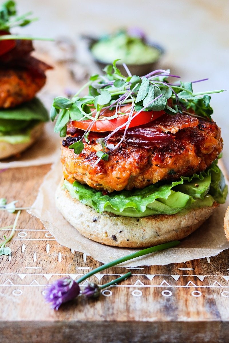 Close up of BLT Salmon Burgers w/ Avocado Chive & Yogurt Aioli ready to serve on a wooden board