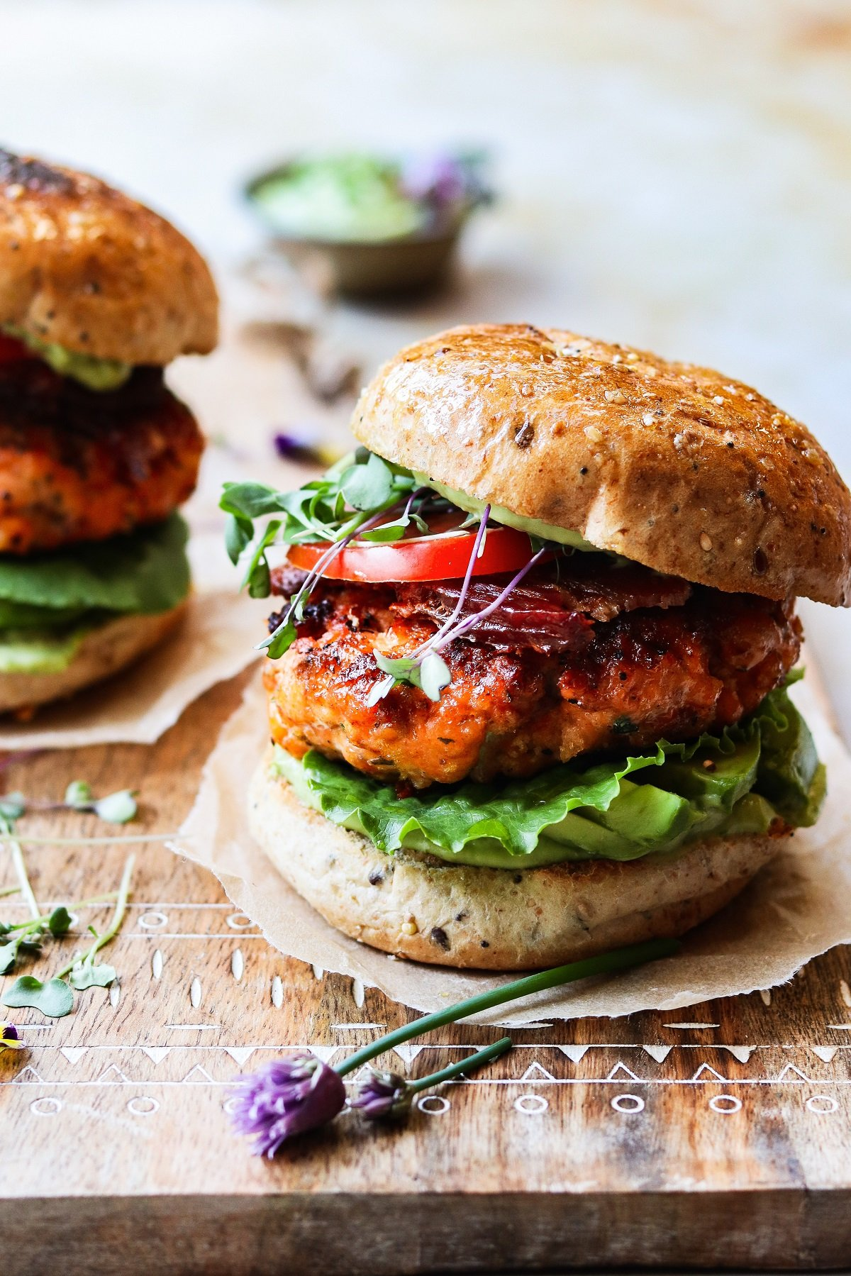 Easy, delicious and tender fresh salmon burgers seared to perfection and topped with a creamy, tangy aioli, crispy bacon, lettuce and tomato all on a toasted bun sitting on a wooden board.