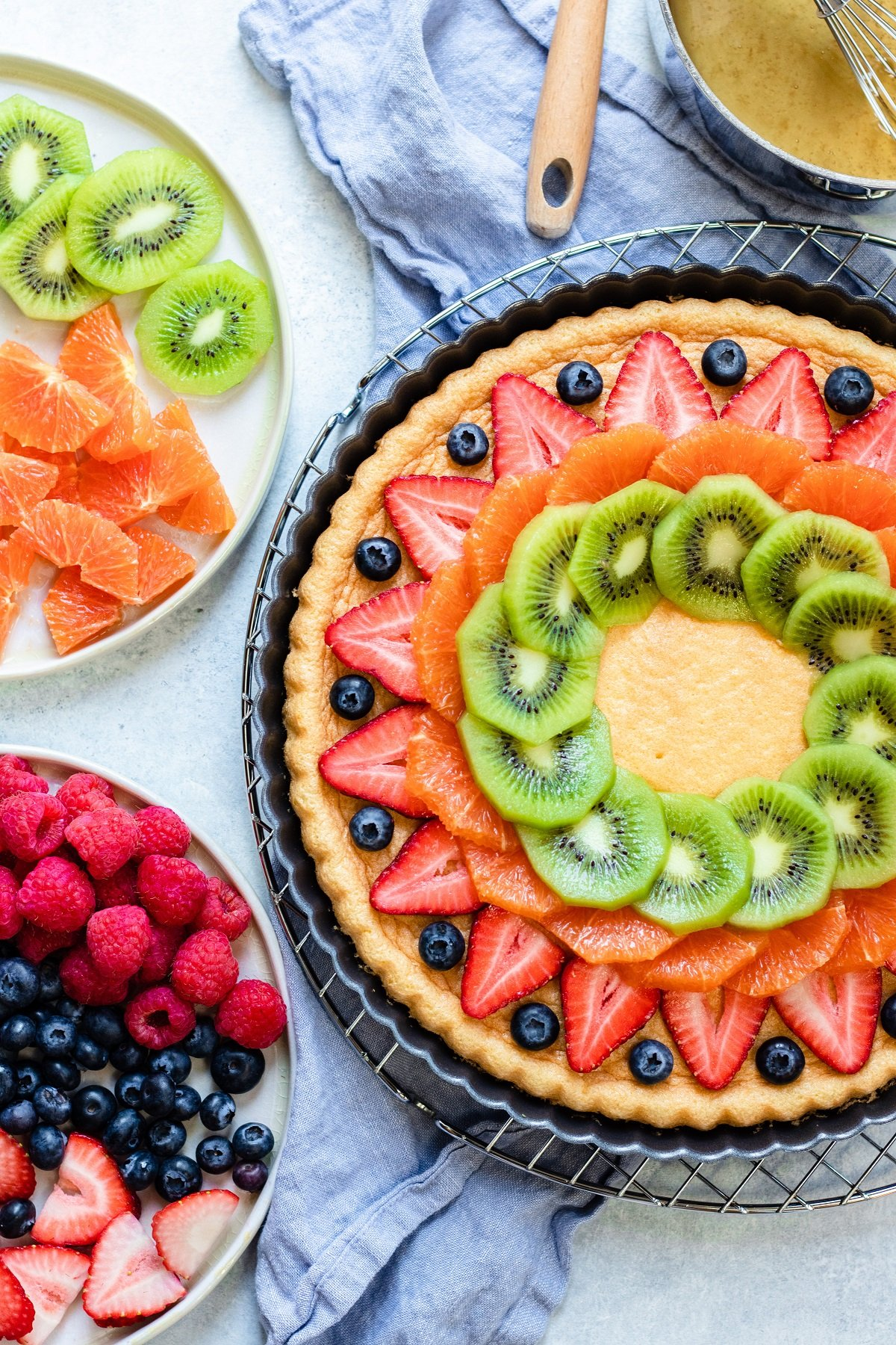 sliced strawberries, kiwi and oranges along with blueberries getting arranged over spongecake