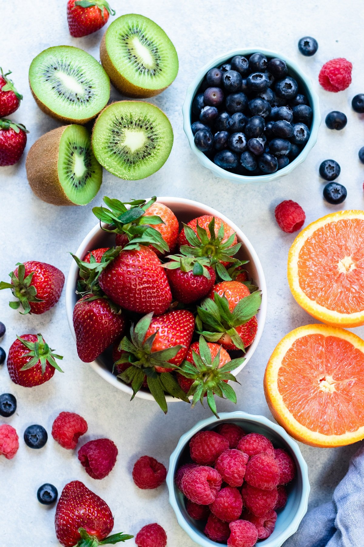 fruit used to decorate flan in bowls on off-white surface - strawberries, raspberries, blueberries, sliced oranges and kiwis