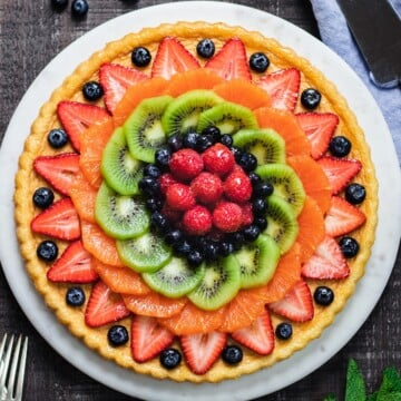 Glazed German Fruit Flan ready to serve on marble cake stand.